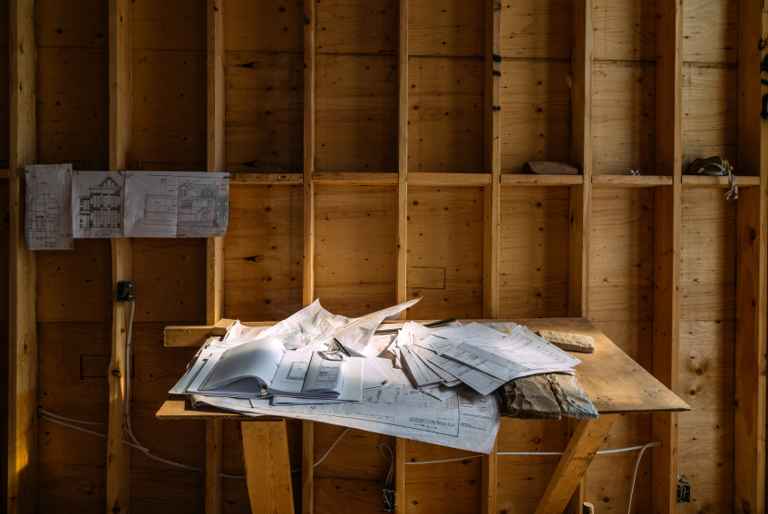 Blue prints and plans for a house on a wooden table in a construction zone