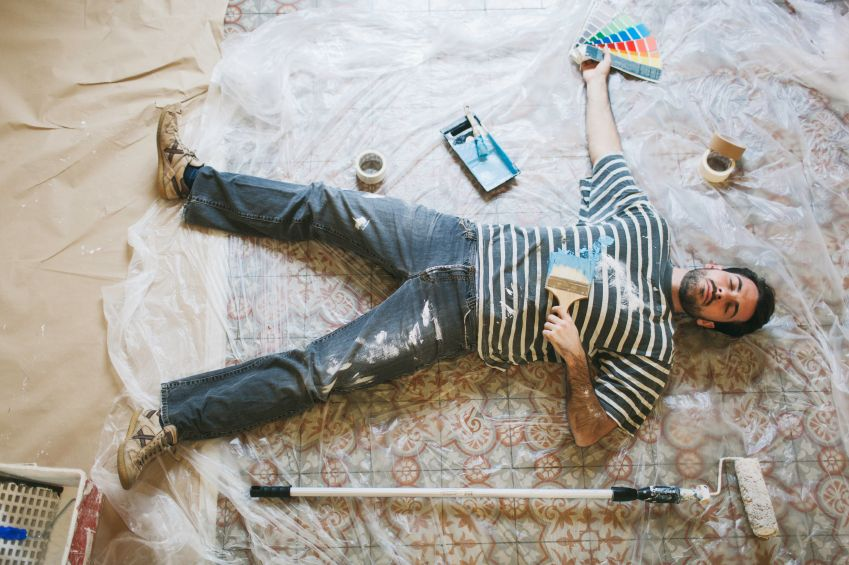 Man burnt out from painting laying on the floor