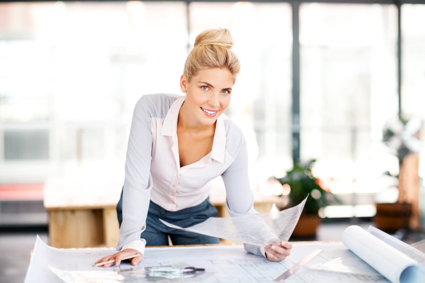 Portrait of confident female surveyor analyzing blueprint at desk in office.