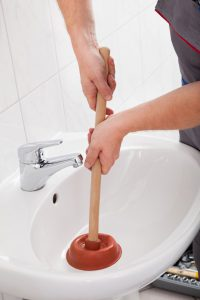 Plumber using plunger in sink