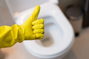Thumbs up with yellow cleaning gloves over toilet