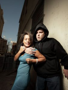 Woman in blue dress defending herself against a man in a hoodie