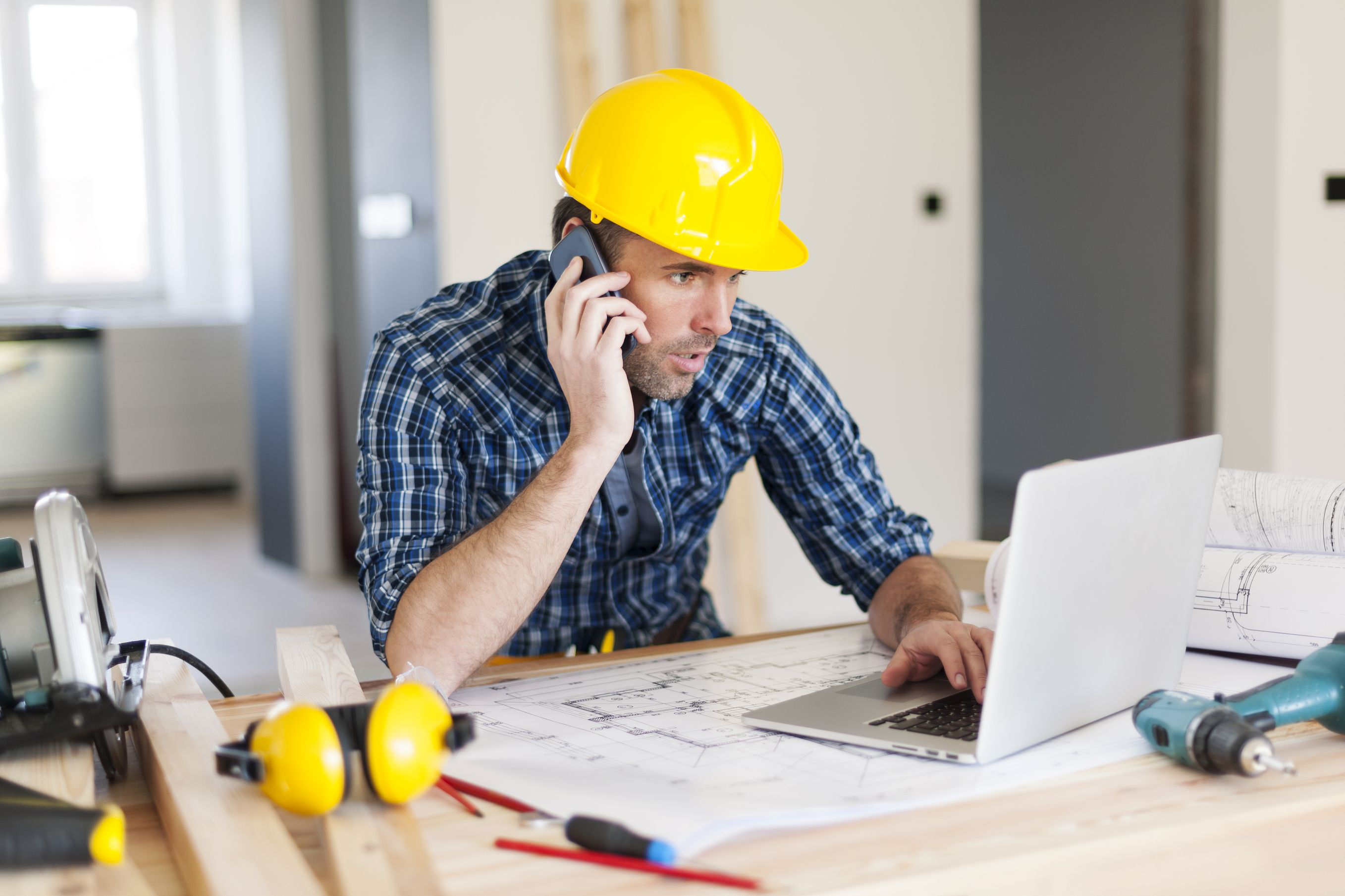 Construction worker using mobile phone and laptop