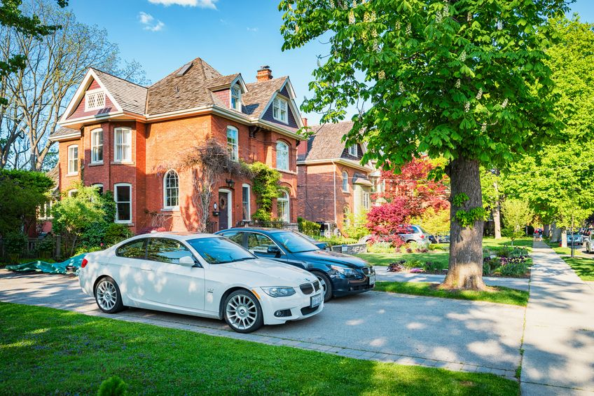 2 cars parked in the side driveway of a two story brick house