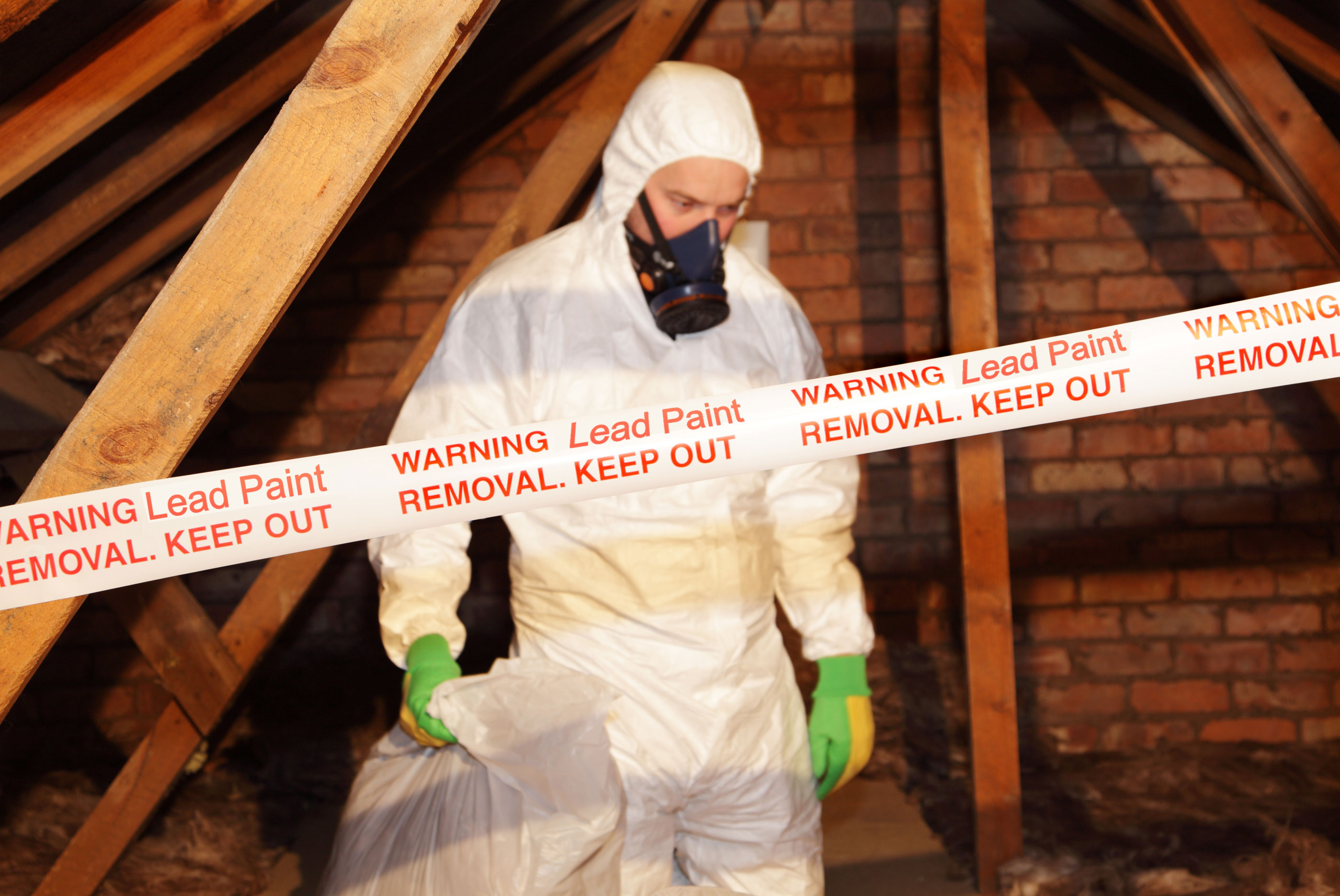 Man in white protective suite and mask in attic moving lead paint