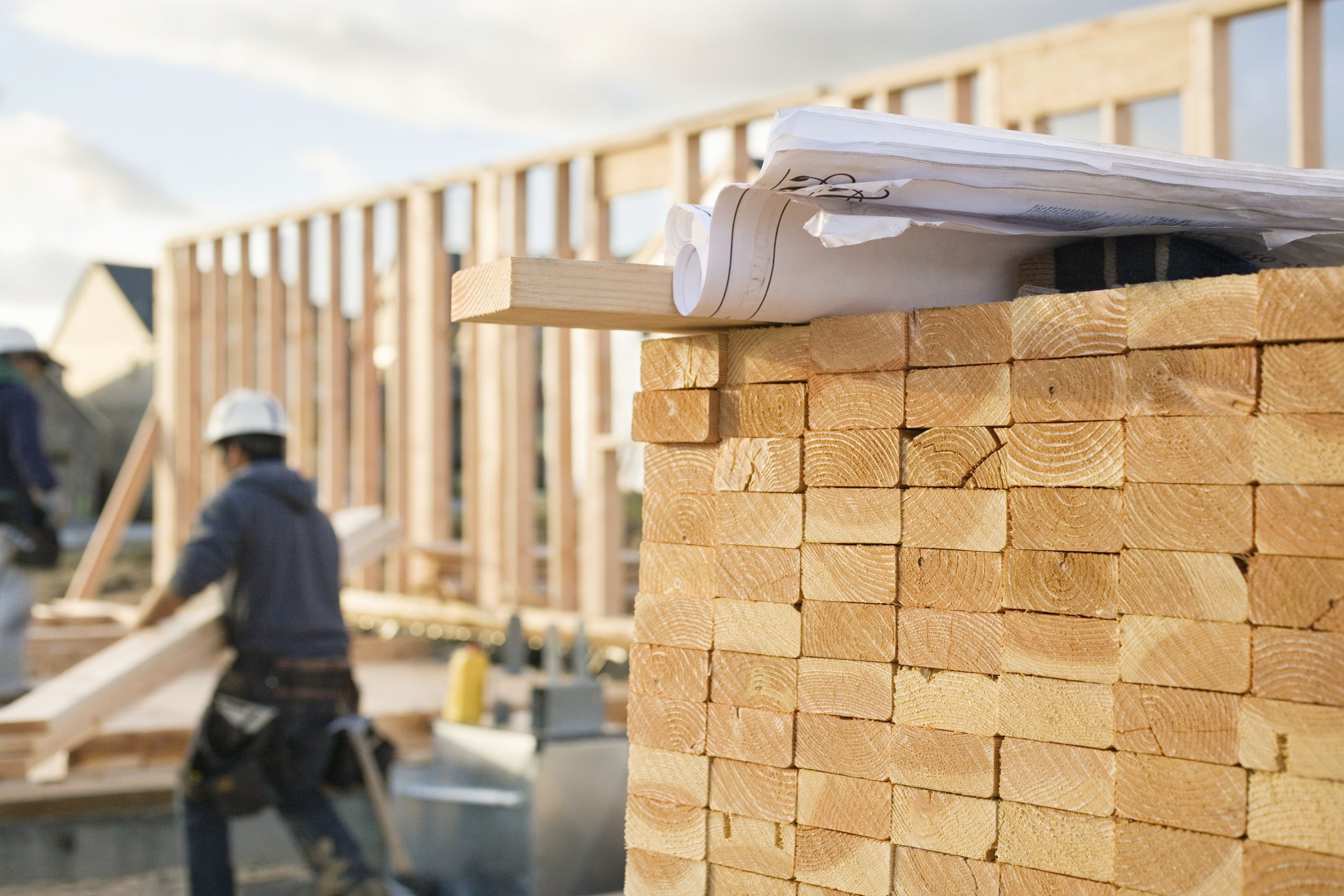 close up of a pile of 2x4's with architect plans on top of them and a worker in the background