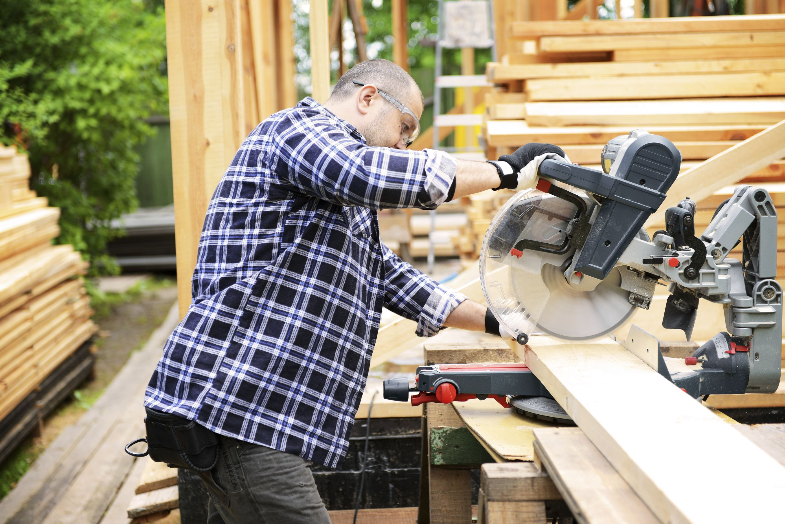 construction worker using table saw cutting wood for project