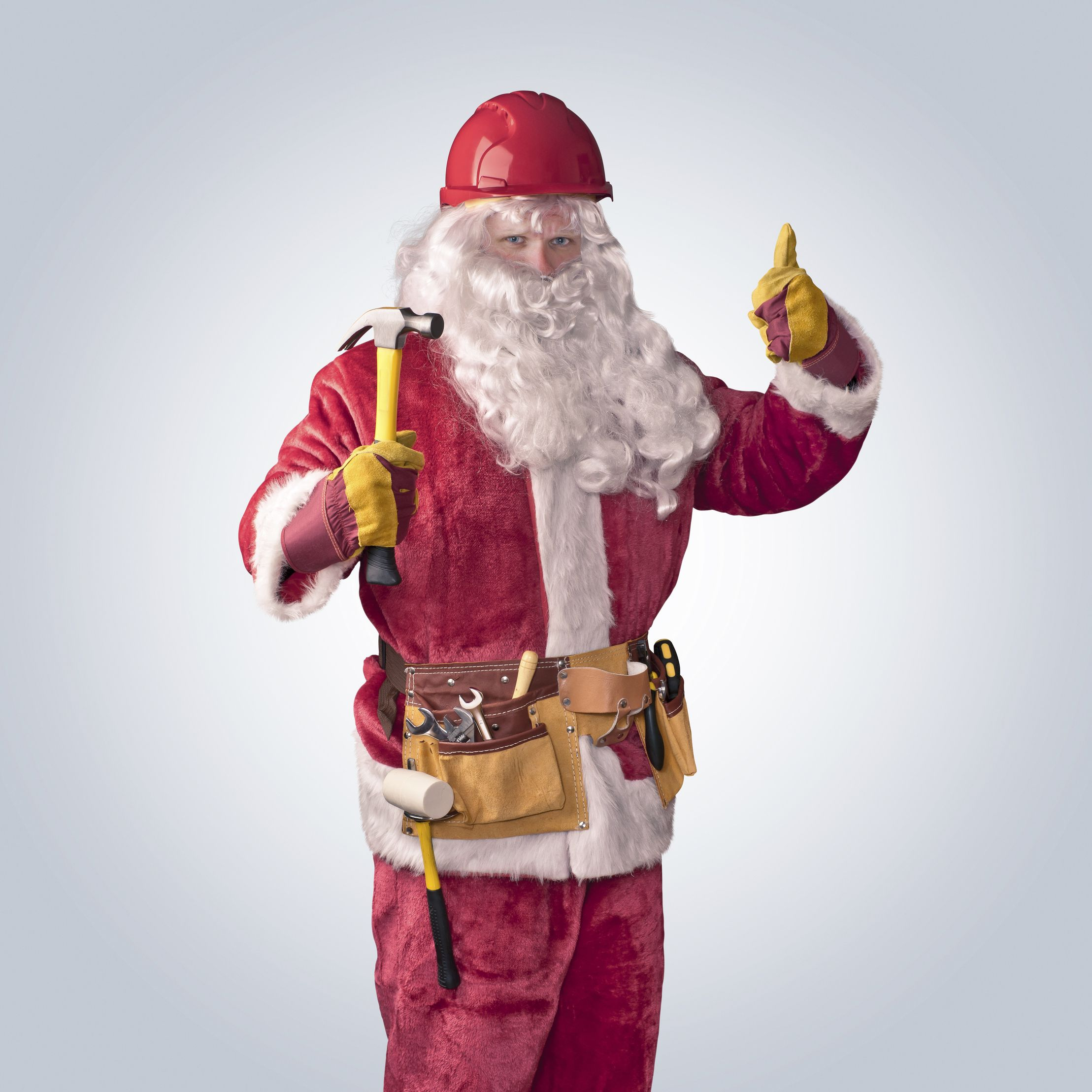 Santa Claus worker in helmet with hammer